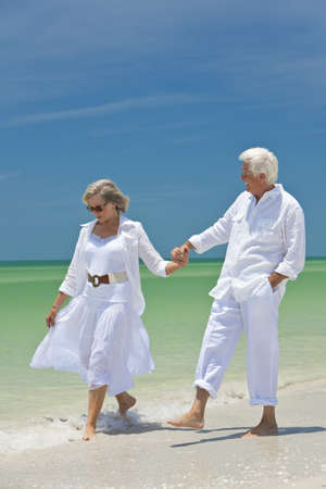 Happy senior man and woman couple walking and holding hands on a deserted tropical beach with bright clear blue sky Stock Photo - 8329832