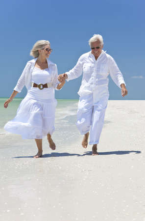 beach clothes: Happy senior man and woman couple running, laughing and holding hands on a deserted tropical beach with bright clear blue sky