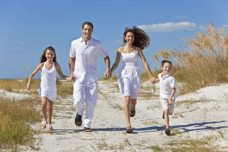 A happy family of mother, father and two children, son and daughter, running holding hands and having fun in the sand of a sunny beach Stock Photo