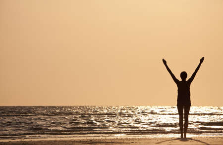 1 person: A young woman standing arms raised at sunset or sunrise on a beach Stock Photo
