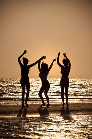 Three beautiful young women in bikinis dancing on a beach at sunset all in silhouette