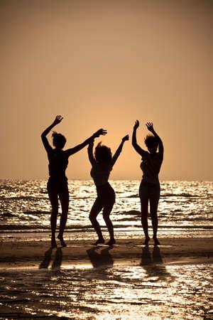 chicas bailando: Tres hermosas mujeres jóvenes en bikinis bailando en una playa al atardecer en silueta