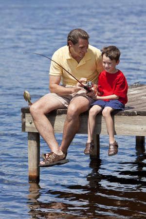 Un padre que enseñar a su hijo de pesca y captura de un pez en un embarcadero fuera en sol de verano Foto de archivo - 8329882