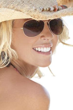 Asombrosamente bella y sexy rubia joven en paja sombrero de vaquero y gafas de sol