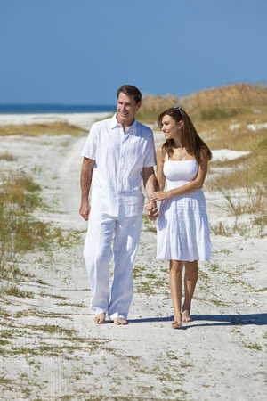 Man and woman romantic couple in white clothes holding hands and walking on a deserted tropical beach with bright clear blue sky photo