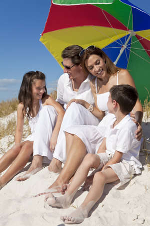parasol: A happy family of mother, father and two children, son and daughter, laughing and having fun in the sand under a colorful umbrella or parasol on a sunny beach
