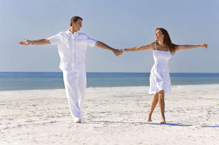 Happy romantic man and woman couple dancing and holding hands on a deserted tropical beach with bright clear blue sky photo