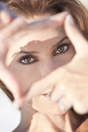 Outdoor portrait of a beautiful young brunette woman with brown eyes looking through her hands making a frame photo