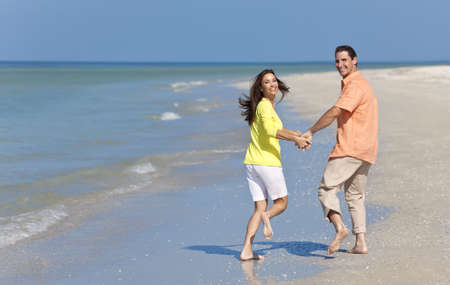 Happy man and woman couple running, laughing and holding hands on a deserted beach with bright clear blue sky photo