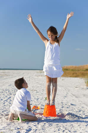 sandcastles: Two young children, boy and girl, briother and sister, playing on a beach making sandcastles