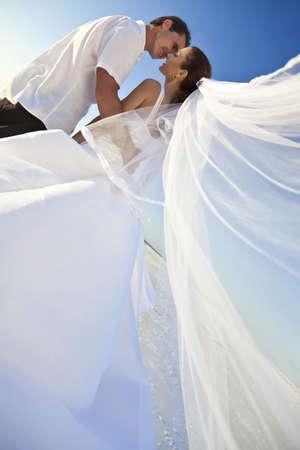 luna de miel: Una pareja casada, la novia y el novio, a punto de besar en el sol en una hermosa playa tropical