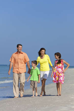 A happy family of mother, father and two children, son and daughter, walking and having fun in the sand of a sunny beach photo