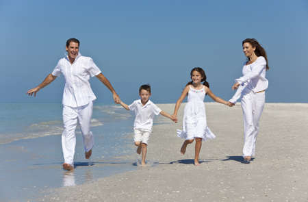 A happy family of mother, father and two children, son and daughter, running holding hands and having fun in the sand of a sunny beach photo