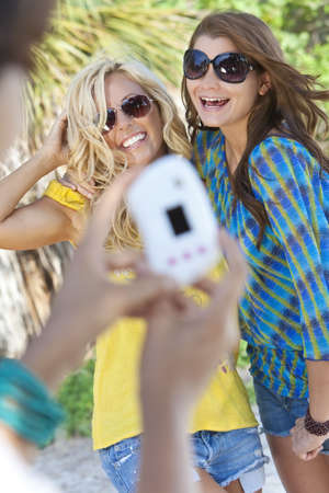 Three beautiful young women in their twenties laughing and having fun taking digital photographs on vacation, shot in golden sunshine in a tropical resort location. photo