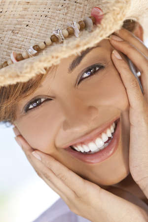 A beautiful mixed race young woman laughing and having fun wearing a straw cowboy hat, shot under a palm tree on a tropical beach photo