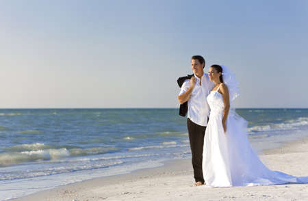 A married couple, bride and groom, together in sunshine on a beautiful tropical beach photo