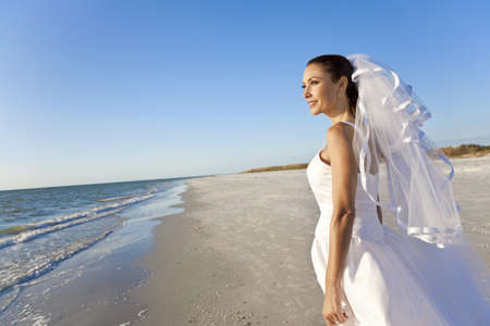 wedding beach: A married woman bride in her wedding dress in sunshine on a beautiful tropical beach