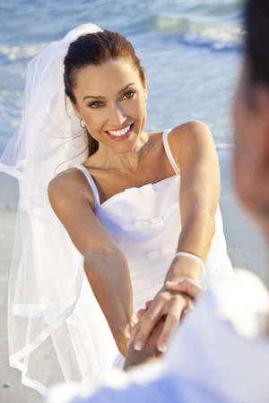 pareja de esposos: Una pareja casada, la novia y el novio, holdong junto las manos re�r y divertirse en la luz del sol en una hermosa playa tropical