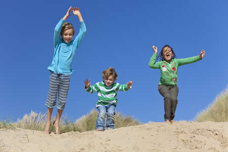 Three children, two blond boys and a mixed race little girl, having fun arms raised and jumping in the dunes of a sandy beach photo