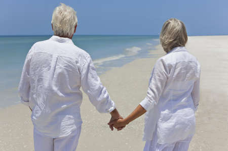 Rear view of a happy senior man and woman couple together holding hands and looking out to sea on a deserted tropical beach with bright clear blue sky Stock Photo - 8548886