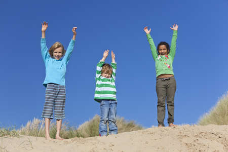 Three children, two blond boys and a mixed race little girl, having fun arms raised in the dunes of a sandy beach photo