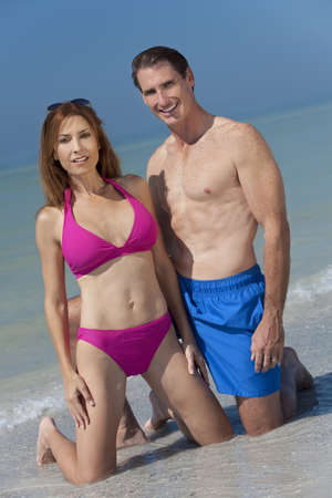 Happy fit and healthy man and woman middle aged couple in swimming trunks and bikini kneeling on a deserted beach with bright clear blue sky photo