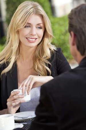 Una mujer joven hermosa y sofisticada con caf� en una mesa de caf� de la ciudad moderna con su amiga un empresario vestido inteligente Foto de archivo