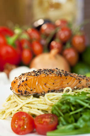 peppered: Peppered salmon fillet with spaghetti pasta tomatoes and green salad Stock Photo