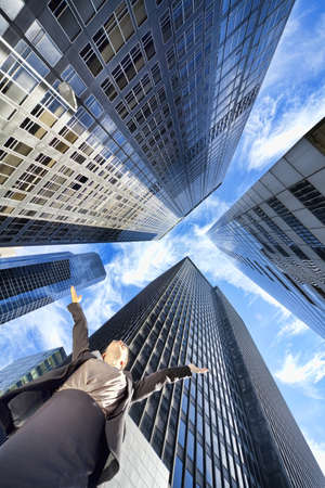 High Dynamic Range HDR photograph if a businesswoman arms raised surrounded by modern city high rise skyscraper office buildings Stock Photo - 8584223