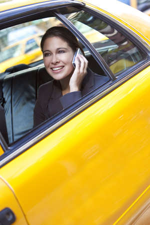 A happy young woman talking on her mobile cell phone in the back of a yellow taxi cab. Shot on location in New York City photo