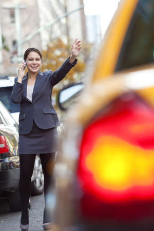 A young woman or businesswoman hailing a yellow Taxi cab while talking on her cell phone in a modern city Stock Photo - 8584215