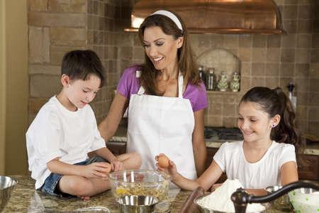 children cooking: Una familia madre, la hija y el hijo sonriente cocinar y hornear galletitas de chocolate en una cocina en el hogar Foto de archivo