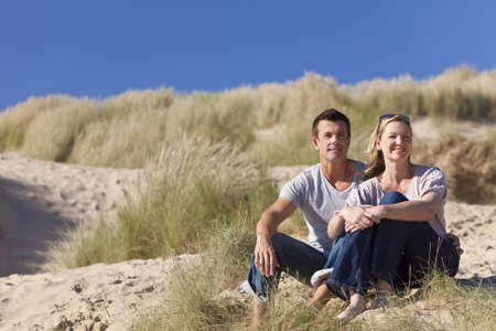 A romantic young man and woman couple sitting together in the sand dunes of a sunny beach with a bright blue sky photo