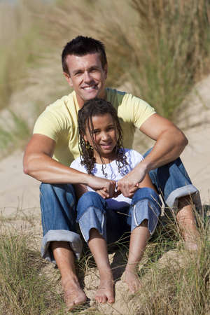 A man and young girl, father and mixed race daughter, sitting in the sand dunes of a sunny beach photo