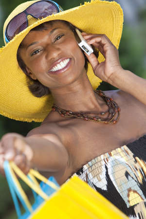 Beautiful and Fashionable African American woman with colorful shopping bags, smiling and talking on her cell phone photo
