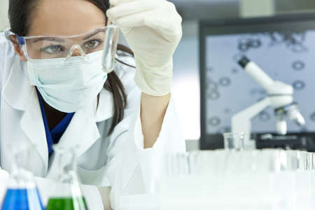scientist: A female medical or scientific researcher or woman doctor looking at a test tube of clear solution in a laboratory with her microscope beside her. Stock Photo