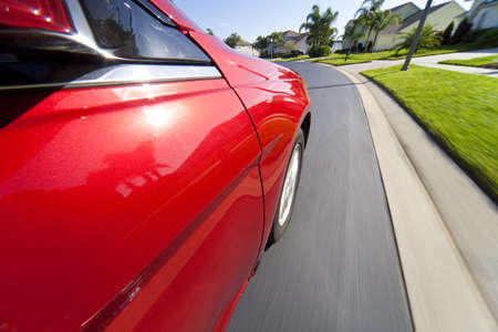 On board camera shot of a red car travelling at speed down a suburban street. Stock Photo - 8710104