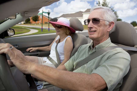 A happy senior couple driving a convertible car wearing sunglasses photo
