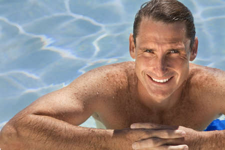wealthy lifestyle: Close up portrait of a handsome and happy mid aged man relaxing resting on his hands at the side of a sun bathed swimming pool smiling with perfect teeth.