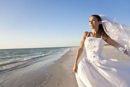 A married woman bride in her wedding dress in golden evening sunshine on a beautiful tropical beach  Stock Photo
