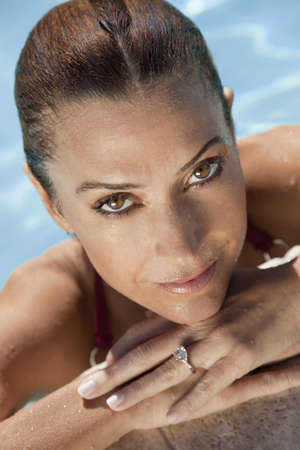 Close up portrait of a beautiful happy woman resting on her hands at the side of a sun bathed swimming pool