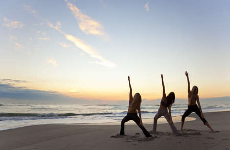 beach sunrise: Three young women in a warrior position practicing yoga on a beach at sunrise or sunset