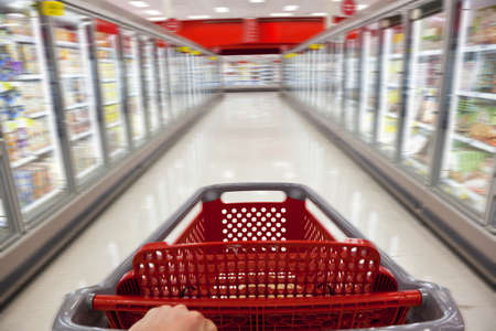supermarket: A fast food concept motion blur shot of a shopping trolley being pushed down the aisle of a supermarket