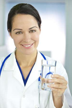 Disparo de concepto comer o estilo de vida saludable de un m�dico de mujeres mujer sonriente celebraci�n y un vaso de agua clara