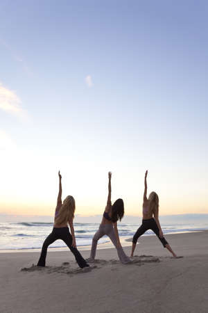Three young women in a warrior position practicing yoga on a beach at sunrise or sunset Stock Photo - 8806666