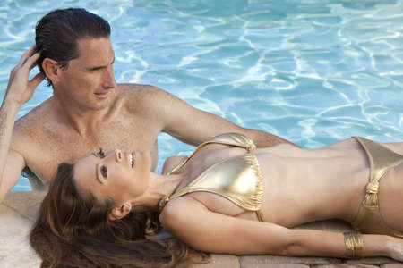 Beautiful happy man and woman couple relaxing by the side of a sun bathed swimming pool