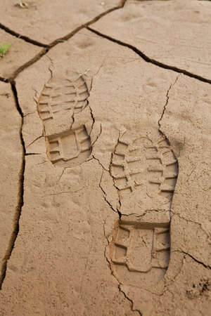 Boot footprints in dry cracked earth photo