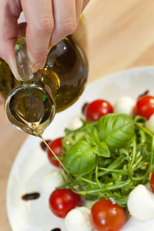 Pouring olive oil salad dressing onto tomato, mozarella and rocket salad with basil garnish and balsamic vinegar photo