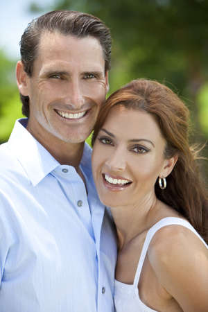 Portrait shot of an attractive, successful and happy middle aged man and woman couple in their thirties, together outside and smiling. photo