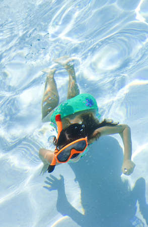 A happy young girl child swimming underwater in a pool wearing orange goggles and snorkel photo